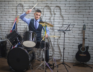 The man plays drums