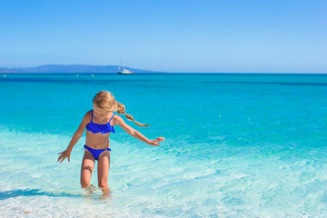 Little girl having fun on tropical beach with white sand and
