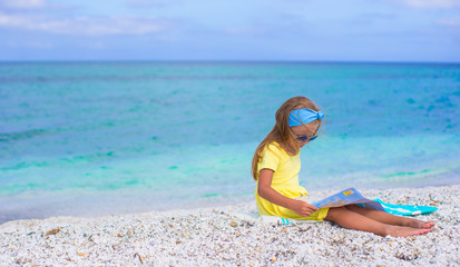 Adorable little girl with map of island on tropical beach