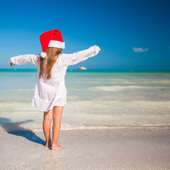 Little adorable girl in red Santa hat during tropical beach