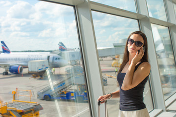 Young woman talking on the phone while waiting for flight