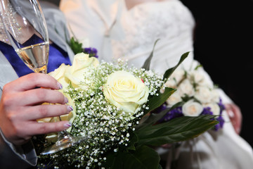 Bridesmaid holding beautiful bouquet and a glass of champagne.