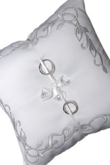 Wedding rings on pillow isolated on white background