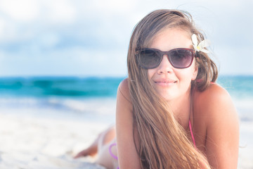 long haired young woman in bikini and sunglasses on tropical