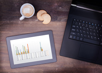 Tablet touch computer gadget on wooden table, graph