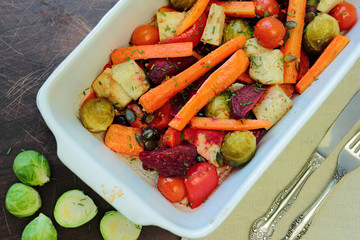 Roasted vegetables in oven with cutlery