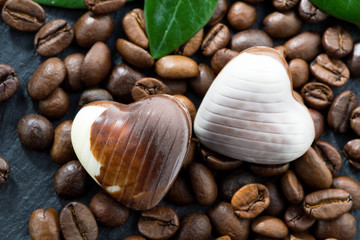 coffee beans and chocolate candies in a heart shape, close-up