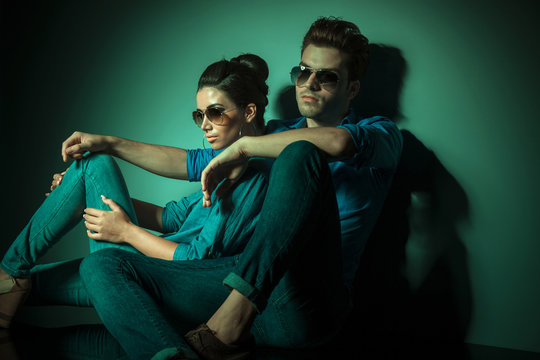 fashion couple leaning on a wall
