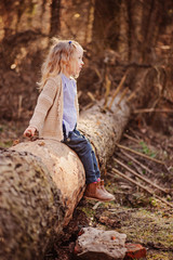child girl sit on tree log on the walk in early spring forest
