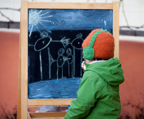 Adorable little boy, drawing summer picture with chalk on a boar