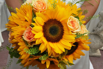 Bride holding a beautiful bouquet made of sunflowers and roses