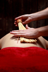 Closeup on young woman receiving hot stone massage