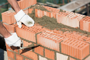 Bricklayer installing bricks and caulking joints with trowel