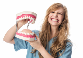 Zahnärztin hält Klappergebiß und grinst