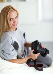 Woman sitting on a sofa in her house with camera
