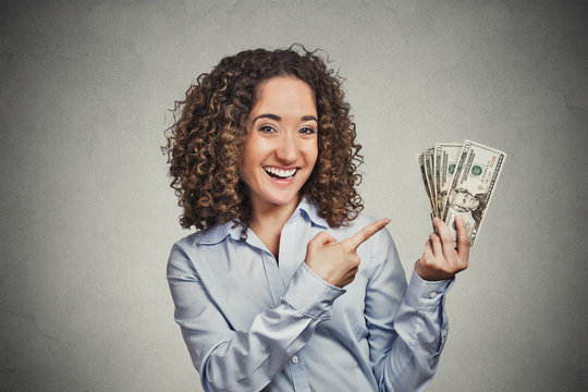 happy successful young business woman holding dollar bills