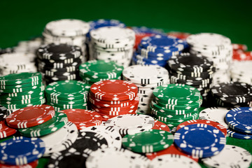 close up of casino chips on green table surface