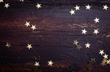 Glitter golden stars on grunge wood background. Holiday Backgrou