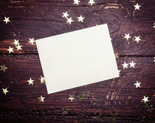 Glitter golden stars  with blank paper on grunge wood background