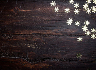 Glitter golden snowflakes on grunge wood background. Holiday Bac
