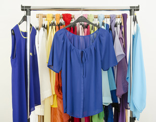 Wardrobe with colorful cute blue outfits displayed on a rack.
