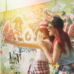 Two happy teenage girlfriends taking a selfie in summer