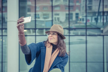 Beautiful young brunette taking a selfie in the city streets