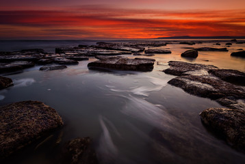 Rocky beach long exposure seascape after sunset Wall mural