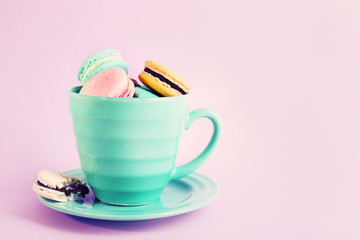 Assortment of gentle colorful macaroons in mug
