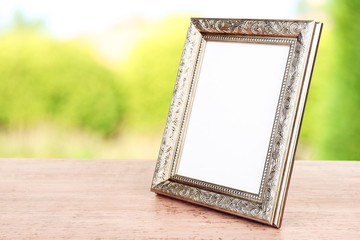 Photo frame on wooden table on nature background