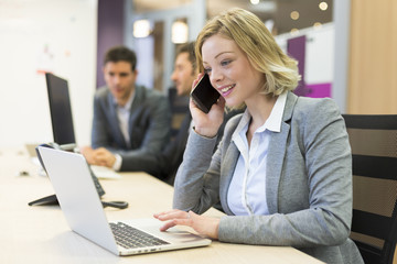 Businesswoman talking on the mobile phone in modern office