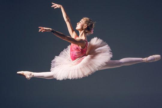 Beautiful female ballet dancer on a grey background. Ballerina