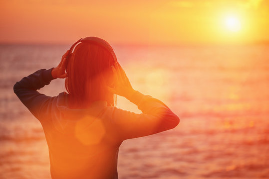 Young woman enjoying beautiful sunset over the sea