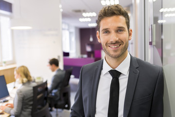 Portrait of smiling Businessman posing  in modern office, lookin