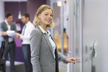 Pretty blond businesswoman open de door in modern office. Concep