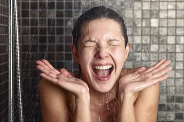 Junge Frau reagiert überrascht auf heißes oder kaltes Wasser