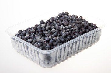 Frozen blueberries in a plastic container on a white background.