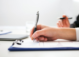 Business person writing on a sheet of paper