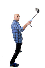 young man taking  smartphone selfie picture holding stick