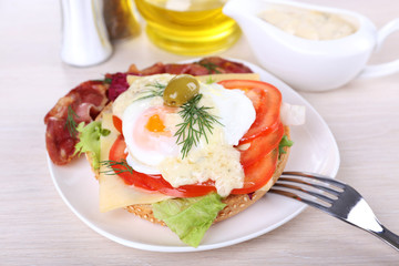 Sandwich with poached egg, tomato and bacon