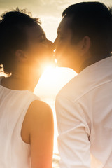 Kissing couple at sun background