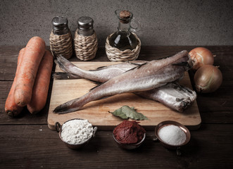 Still life with fish, vegetables and spices on a wooden board. T