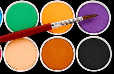 paints of different colors and slim paintbrush (brush)