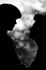 Romantic silhouette of a couple in black and white bokeh.