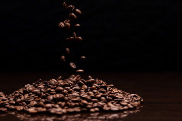 High contrast image of coffee beans being dropped onto pile with