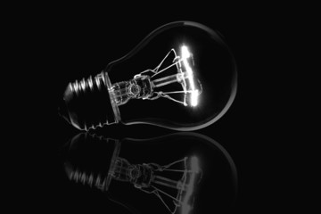 Light bulb and reflection isolated black background