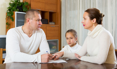 Sad family of three with documents