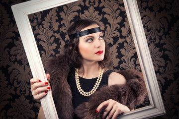 beautiful retro woman posing with white wooden frame against vin