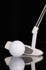 Golf putter and gold equipments on the black glass desk
