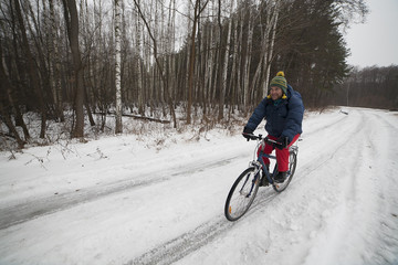 View of a cyclist in winter forest